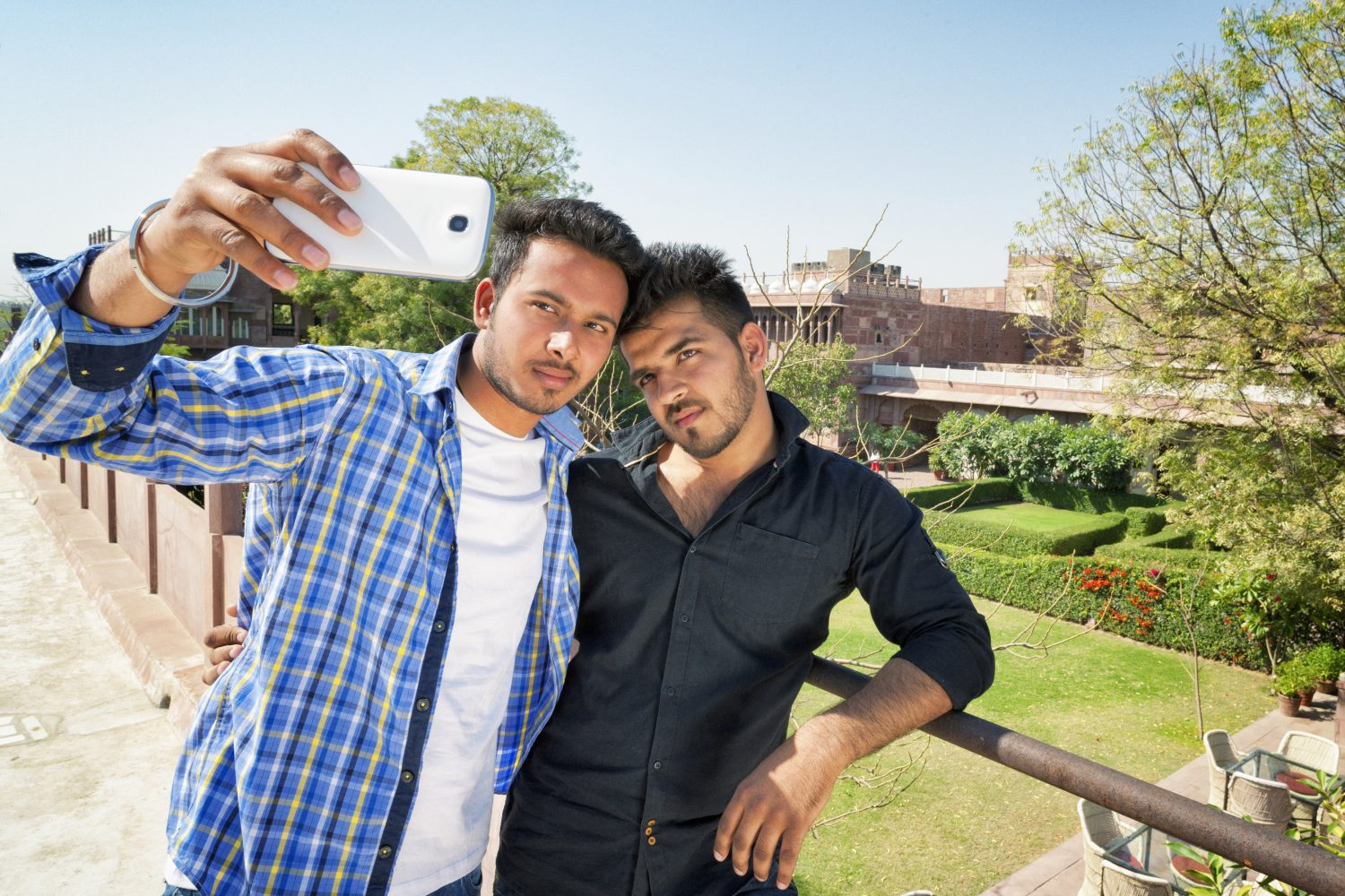 Two young Indian men taking a selfie together.